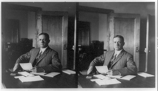 [Earl Rogers, half-length portrait, seated at desk]