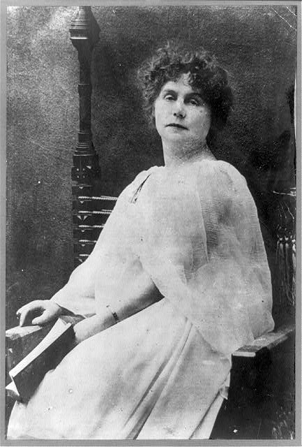 [Marie Corelli, three-quarter length portrait, seated, holding book, facing front]