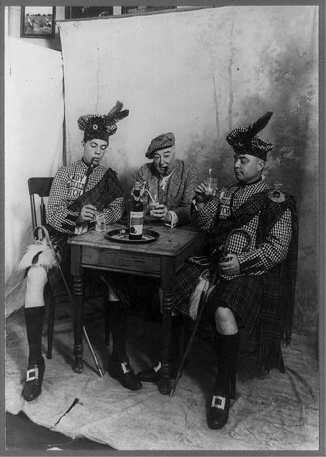 [Two men wearing kilts and man smoking cigar, seated at small table drinking Sandy MacDonald scotch]