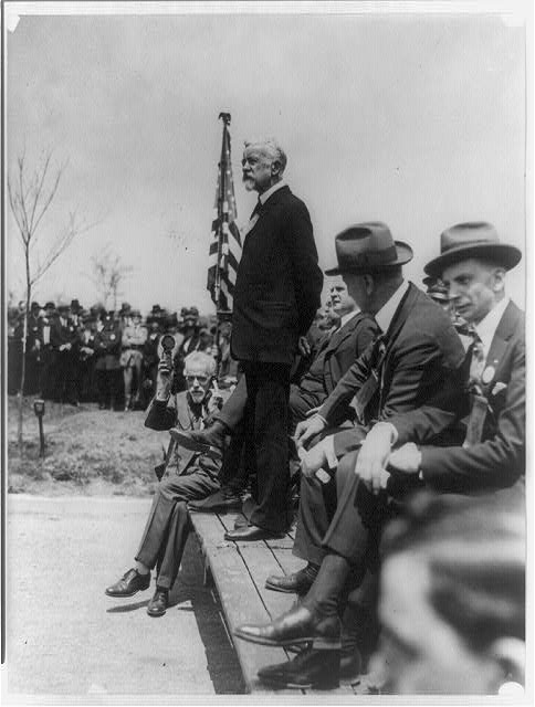 [Henry Cabot Lodge standing on platform outdoors making a speech; man seated on platform with hearing aid or recording device]