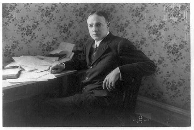 [Billy Sunday, three-quarter length portrait, seated at desk, facing left]