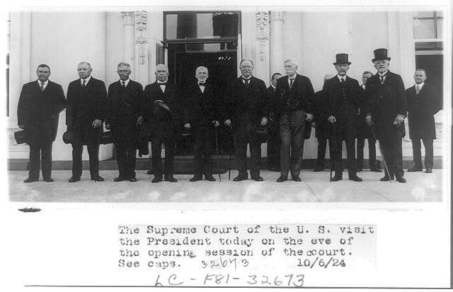 [Nine justices of the United States Supreme Court posed standing outdoors with William Howard Taft on eve of opening session of the court]