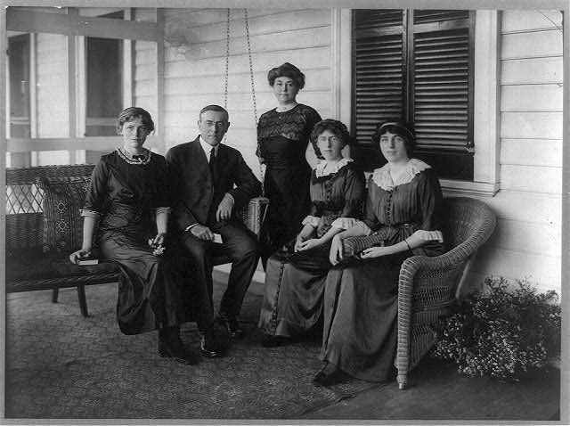 [Woodrow Wilson, seated posed on swing on porch, facing front, with his wife and three daughters]
