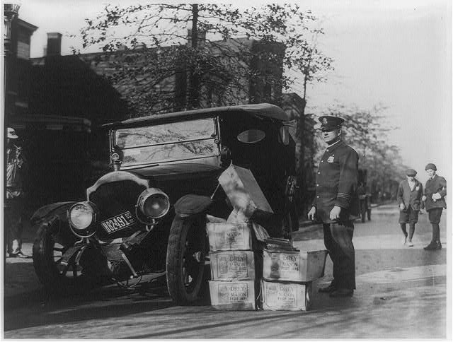 [Policeman standing alongside wrecked car and cases of moonshine]