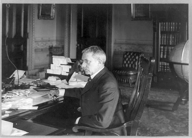 [Elihu Root, half-length portrait, seated at desk, facing left]