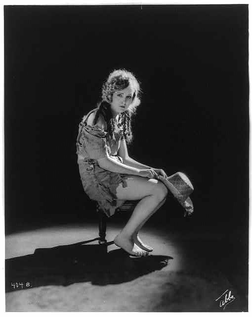 [Young woman in ragged clothes seated on stool in Mack Sennett comedy film]