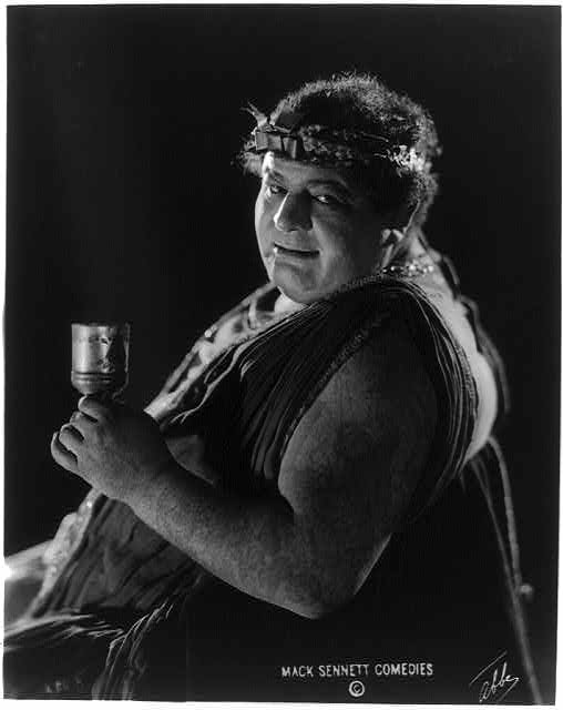 [Actor from Mack Sennett comedy film in Roman toga seated holding wine glass]