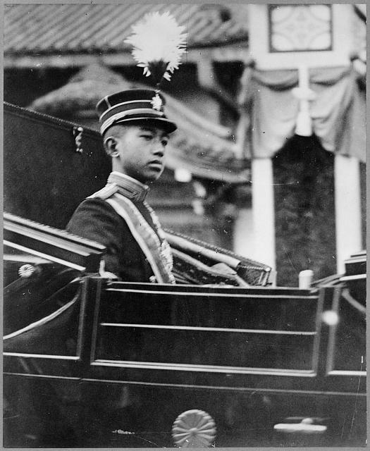 [Hirohito, Emperor of Japan, half-length portrait, facing right, seated in carriage with chrysanthemum emblem on the door]