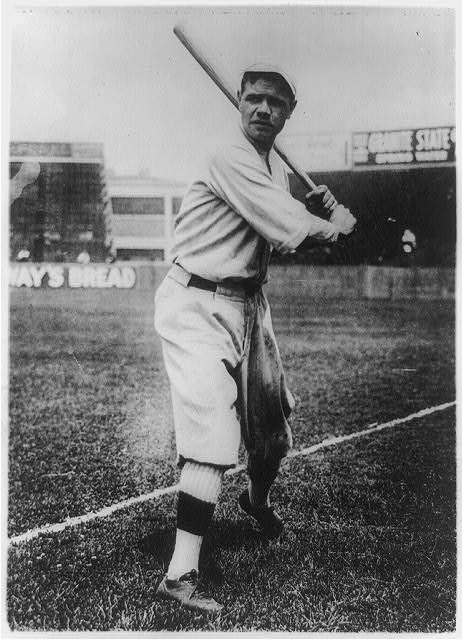 [Babe Ruth, full-length portrait, standing, facing front, holding up bat, in baseball uniform, on field]