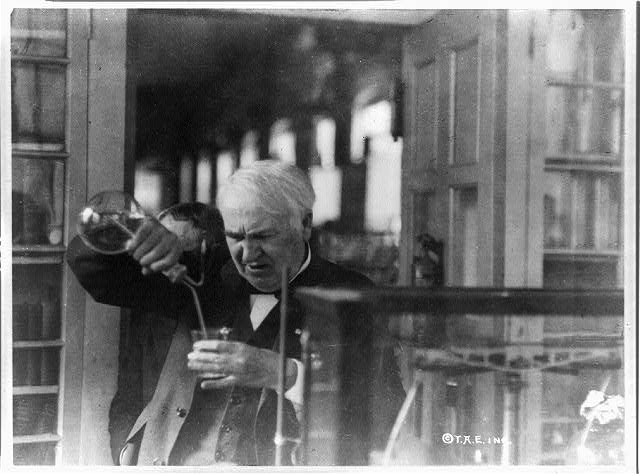 [Thomas Edison, half-length portrait, facing left and looking down into glass, experimenting in his laboratory]