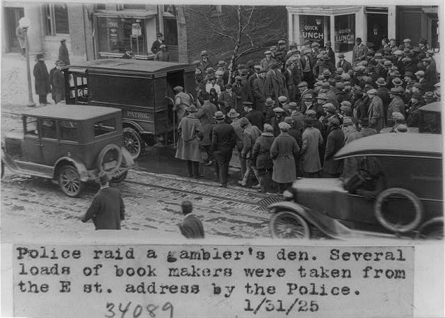 Police raid a gambler's den. Several loads of book makers were taken from the E. St. address by the police