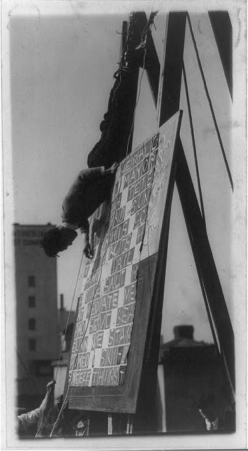 Harry Kahne, mental marvel and daredevil from Keiths Theatre, amuses the cross word puzzle fans as he works a puzzle backwards, while being hung from the top of one of Washington's tall office buildings