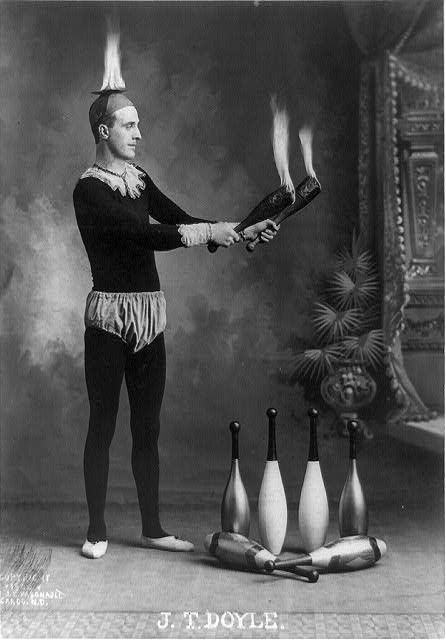 J.T. Doyle [holding 2 burning juggling clubs]