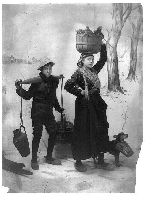 [Dutch girl, boy and dog carrying supplies in snow]