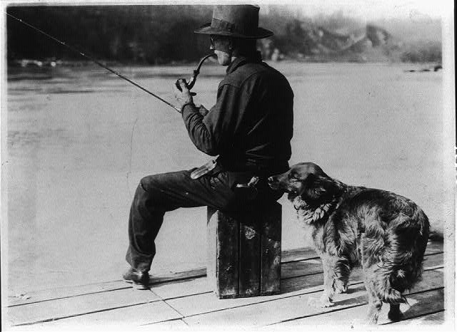 [Hooch Hound, a dog trained to detect liquor (as suggested to Commissioner Haynes by a prohibition agent in Colorado), sniffs at flask in back pocket of man, seated, fishing on pier on the Potomac River]