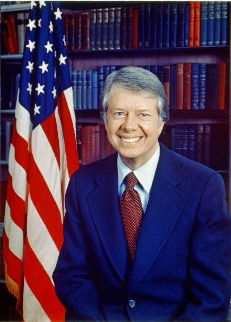 [Jimmy Carter, head-and-shoulders portrait, facing front, next to an American flag]