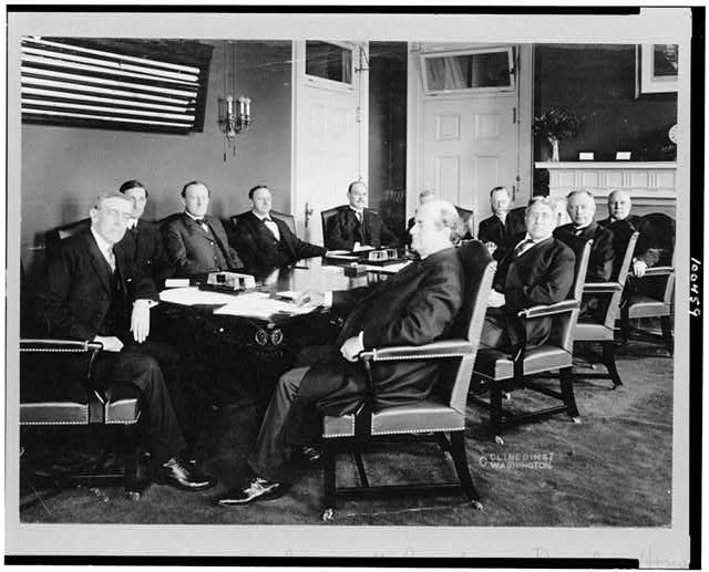 [Woodrow Wilson and his cabinet seated around table]