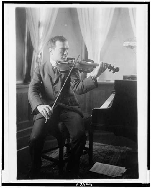 [Bronislaw Huberman, full-length portrait, seated, facing right, playing violin]