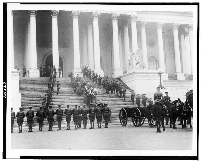 [Coffin of the Unknown Soldier being brought down steps of the U.S. Capitol, where horse-drawn wagon awaits; military personnal stand at attention]