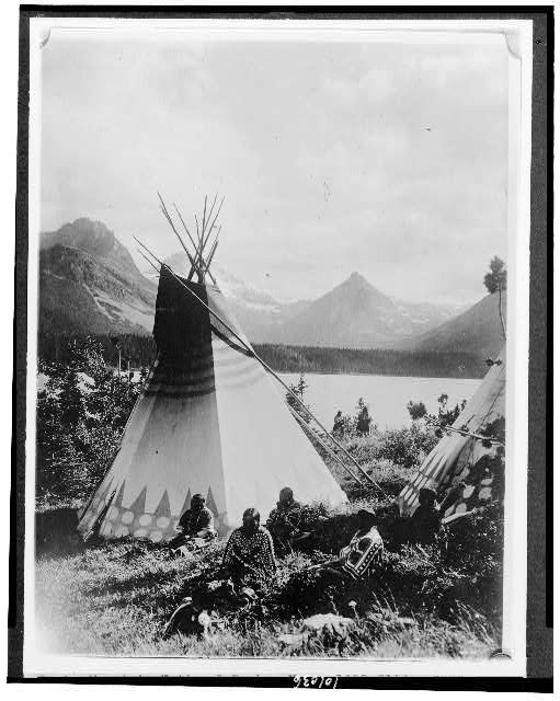 [Indian with two tepees beside a lake in Rocky Mountain National Park, Colorado]