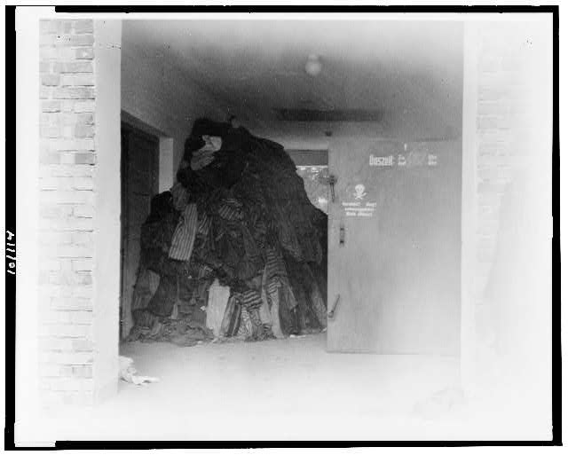 [Stack of clothing, primarily prison uniforms, in an unidentified German concentration camp]