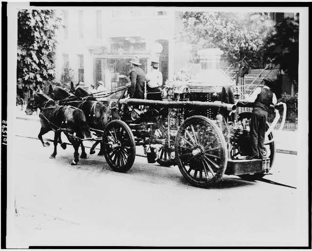 Three firemen on fire engine drawn by three horses in D.C. (1912)