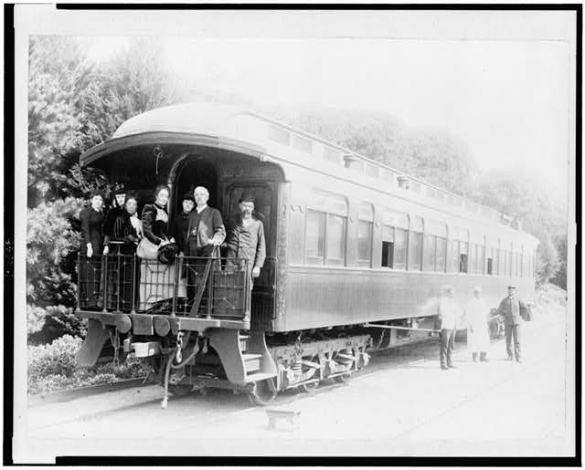 [Henry M. Stanley and party standing on back of train at Monterey, California, March 19th, 1891, porters standing at side of car]