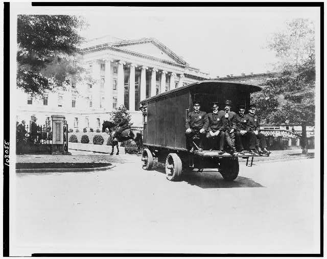 [Five policemen sitting on back of van and policeman on horseback; outside south side of the Treasury Building, Washington, D.C.]