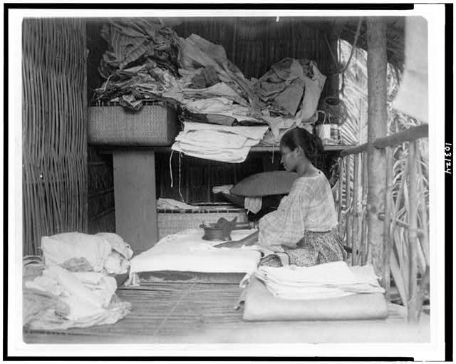 [Javanese(?) woman sitting in room working with textiles at exhibit featuring foreign participants at the World's Columbian Exposition, Chicago, Illinois]