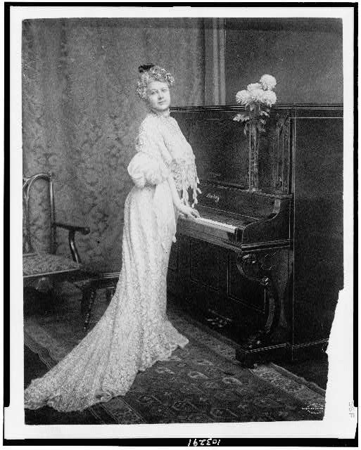 [Woman standing at piano]