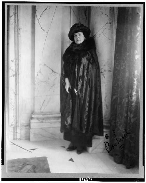 [Alva E. Belmont, full-length portrait, standing, leaning against column, facing slightly left dressed in cape with fur neckpiece, hat]