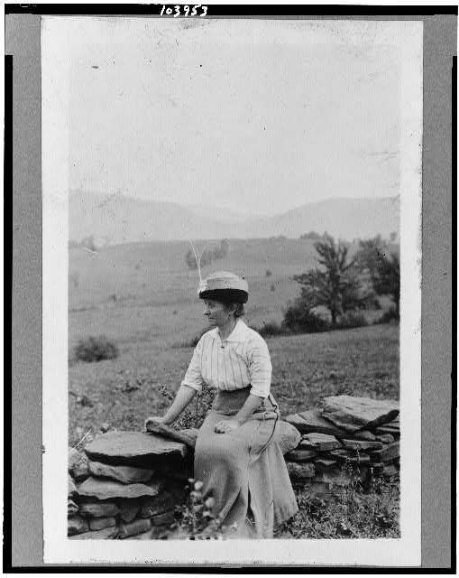 [Dr. Clara Barrus seated on stone fence at Woodchuck Lodge]