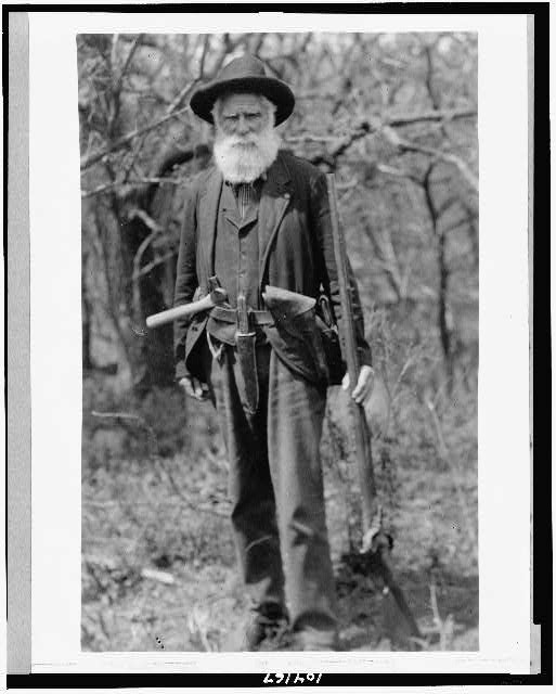 [Daniel Freeman standing, holding gun, with hatchet tucked in belt]