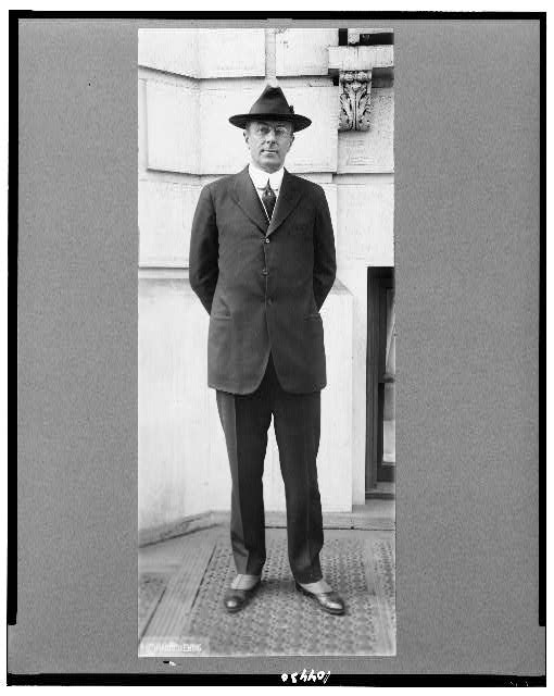 [Homer Stillé Cummings, full-length portrait, standing, facing front with hand behind back, wearing hat]