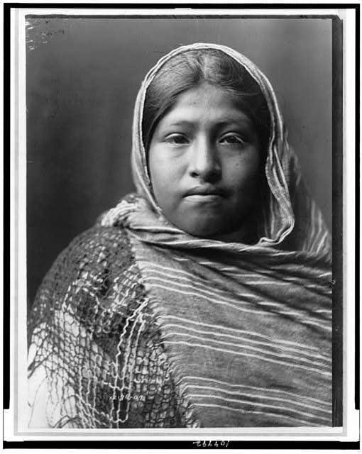 [Yaqui girl, head-and-shoulders portrait, facing front, with striped shawl draped around shoulders and over head]