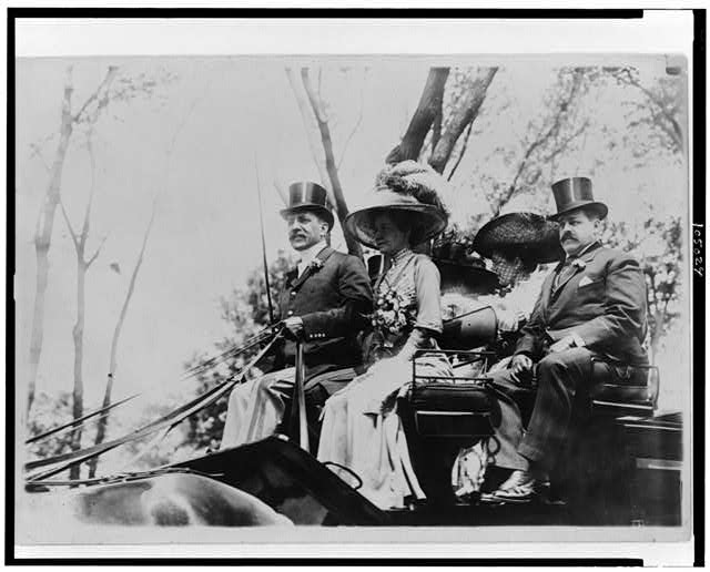 [Harris Charles Fahnestock seated in carriage next to woman in plumed hat (possibly his wife) with another couple at the back of the carriage]