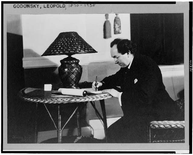 [Leopold Godowsky, three-quarter length portrait, seated at rattan table with lamp, facing left, writing]