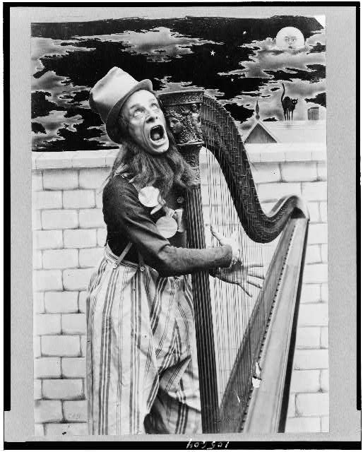 [Oscar Girard, three-quarter length portrait, standing, facing right, in costume, playing harp]