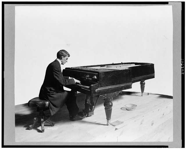 [Robert Harkness, full-length portrait, seated at piano, facing right]