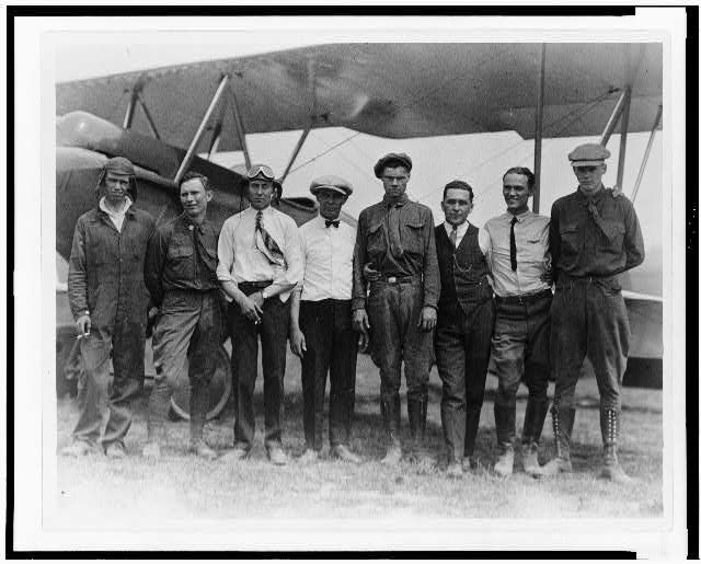 [Charles Lindbergh with seven other men, including Bud Gurney(?), in front of biplane, Lambert-St. Louis Field, 1923]