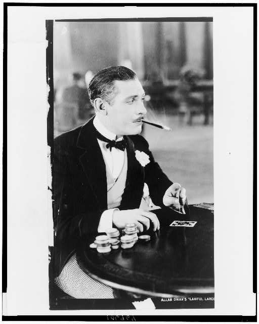 [Man, with cigarette holder in mouth, playing cards]