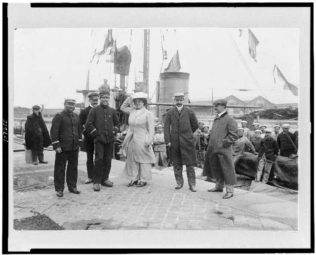 [Louis Blériot with his wife on return to Calais, France, with ship behind them]