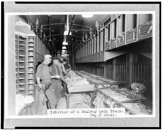 [Men working in a railway mail train]