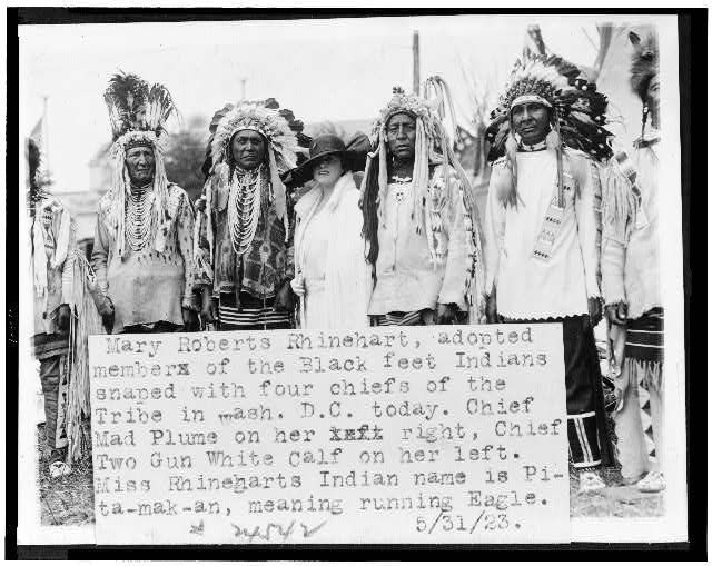 Mary Roberts Rhinehart [sic], adopted member of the Blackfeet Indians snaped [sic] with four chiefs of the tribe in Wash. D.C. today.  Chief Mad Plume on her right, Chief Two Gun White Calf on her left ...