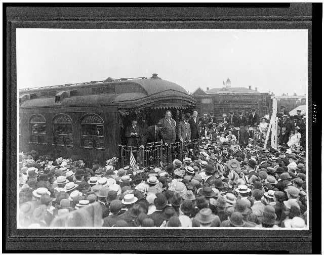 [William H. Taft, full-length, standing on back of train, surrounded by crowd, during campaign tour]