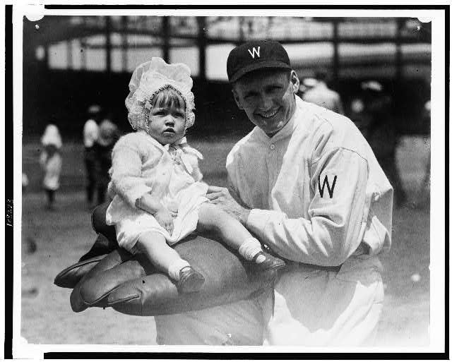[Walter Johnson, half-length portrait, facing slightly left, holding little girl on large glove]