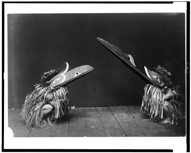 [Kotsuis and Hohhug--Nakoaktok, wearing ceremonial dress, with long beaks, on their haunches, dancing(?)]
