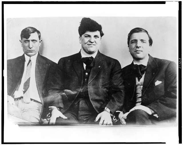 [Left to right: Joseph Caruso, Joseph J. Ettor, and Arturo Giovannitti, half-length portraits, seated, in handcuffs]