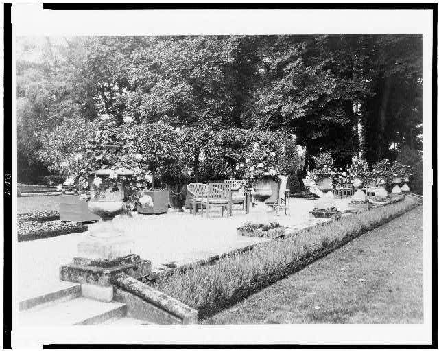 [A Shaded gravelled terrace, screened by orange trees, with chaise lounges, settees and tables, at Pavilion Colombe, Mrs. Edith Wharton's villa, St. Brice-sous-Forêt, France]