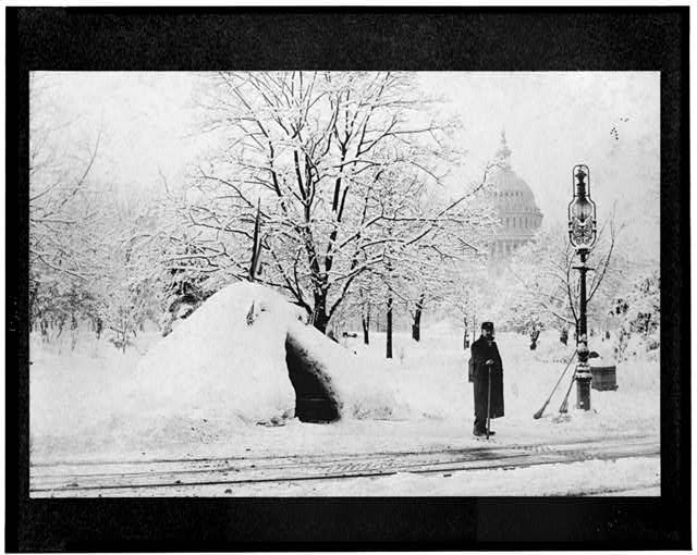 [ Man standing by snow hut, after blizzard of 1888(?), with U.S. Capitol in background, Washington, D.C.]
